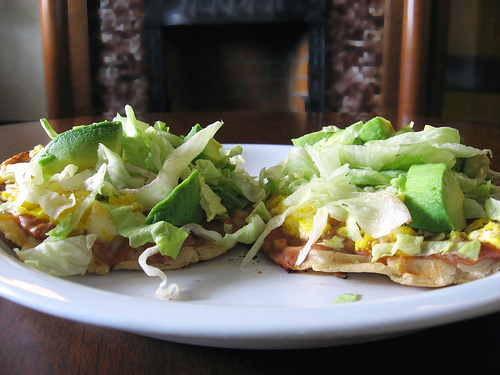 Sopes: thick tortilla with topping of meat, vegetables and sauces