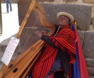 Blind harpist in Ollantaytambo ruins, Peru