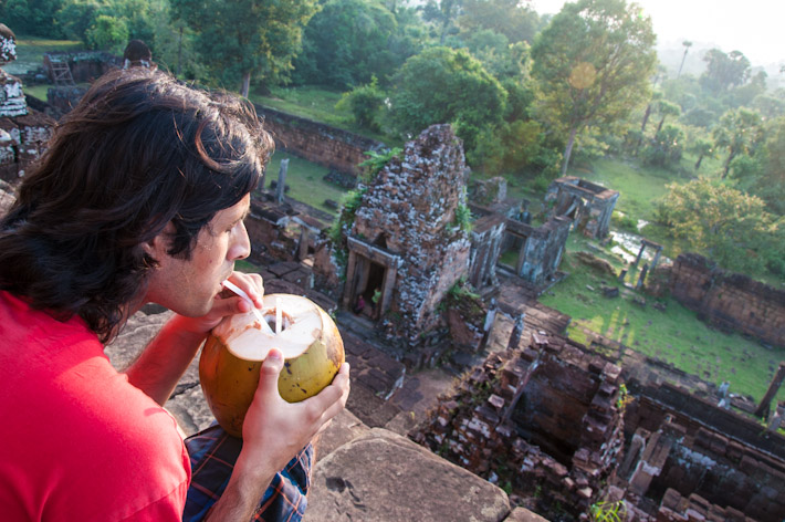 Ashray enjoying a young coconut as the sun goes down near Angkor Wat