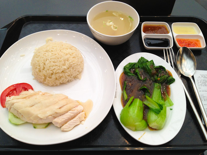 Hainanese chicken with rice, pak choi in soy sauce, a cup of chicken broth and plenty of topping to season it all