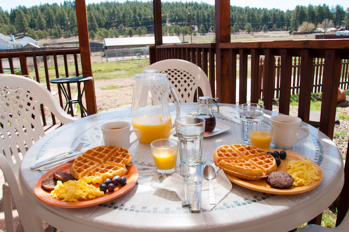 Waffles, scrambled eggs, breakfast meat patty, grapes, OJ and coffee in Flagstaff, Arizona