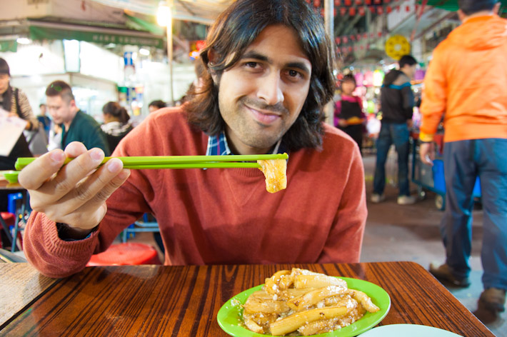 Ashray eating garlic fried eggplant at a night market in Kow Loong