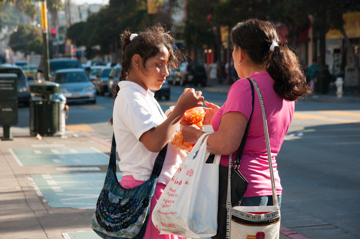 Mom and daughter share some sliced mangoes in The Mission