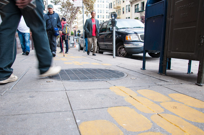 Yellow signs on the floor lead the way to school in the Tenderloin
