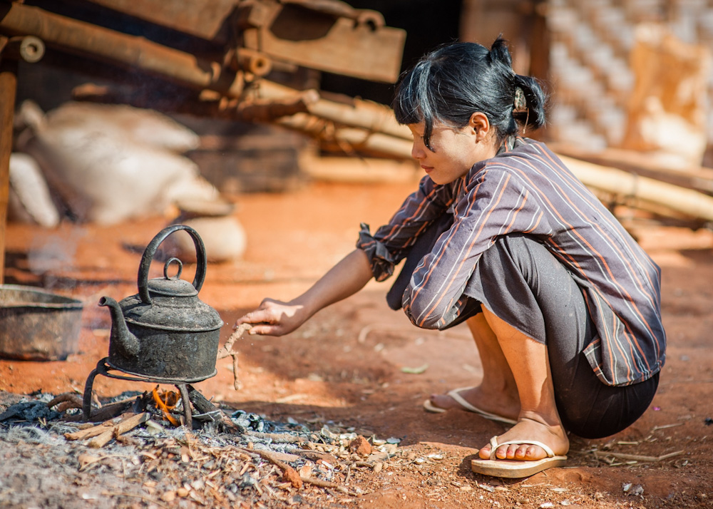 Burmese woman cooking with firewood
