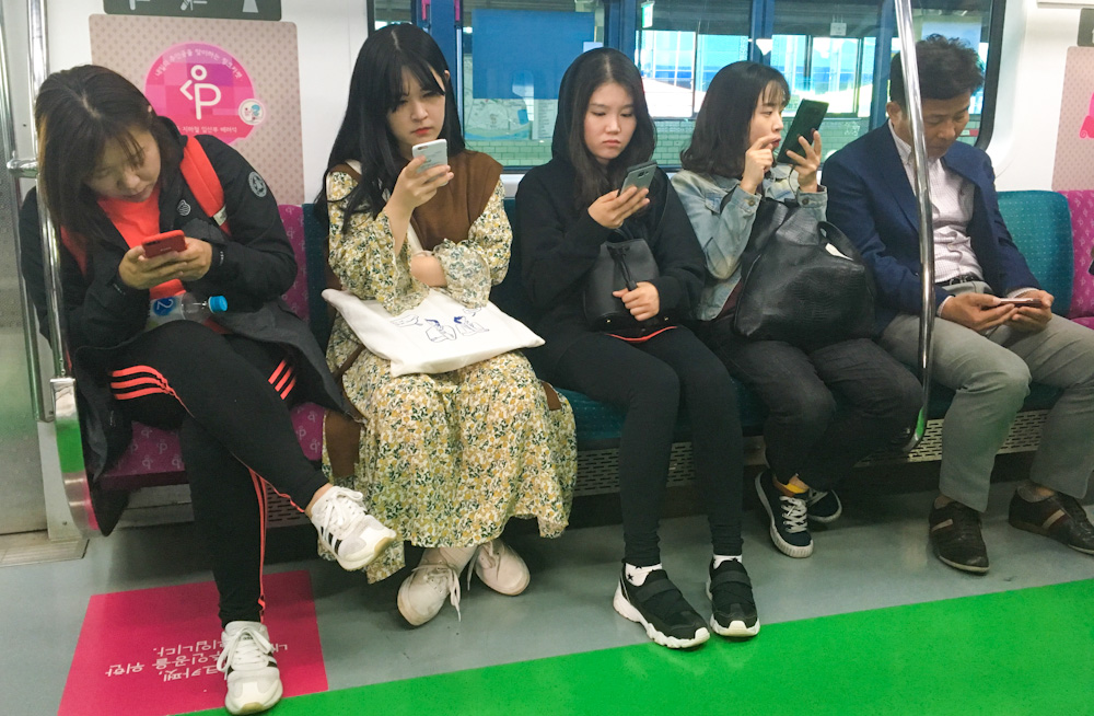 Koreans using their phones while commuting